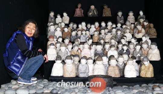 무대미술가 이병복씨가 108명 동자승의 108가지 표정을 보여주는 작품'초심'옆에 앉았다.