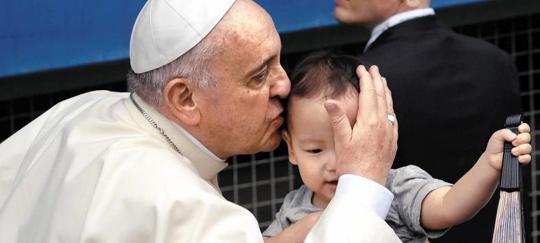 프란치스코 교황이 15일 대전 월드컵경기장 성모승천대축일 미사에 입장하던 중 한 어린이의 이마에 입을 맞추고 있다.