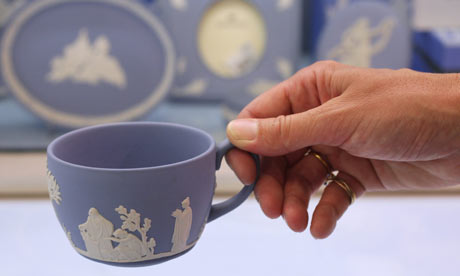 A woman lifts a Wedgwood teacup in the Waterford Wedgwood flagship store in London