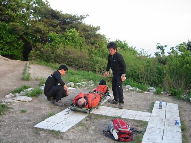 광교산 산악구조대원들이 산정상에서 부상을 당한 등산객을 헬기로 후송시키기 위해 산악용 들것에 고정시키고 있다. 1.jpg