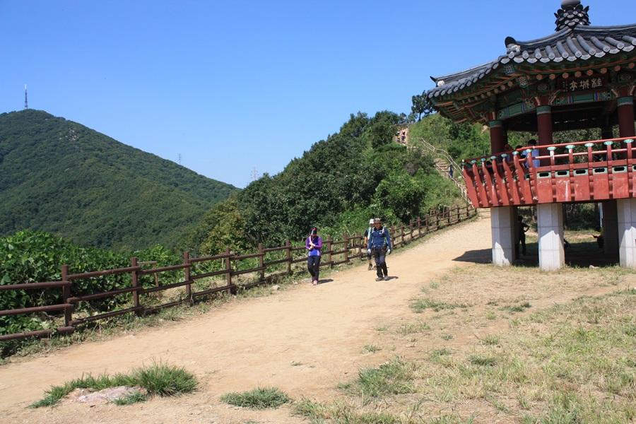계산정에서 등산객들이 휴식을 취하고 있으며, 맞은편에는 우뚝 솟은 송신탑과 함께 계양산 정상이 보인다.