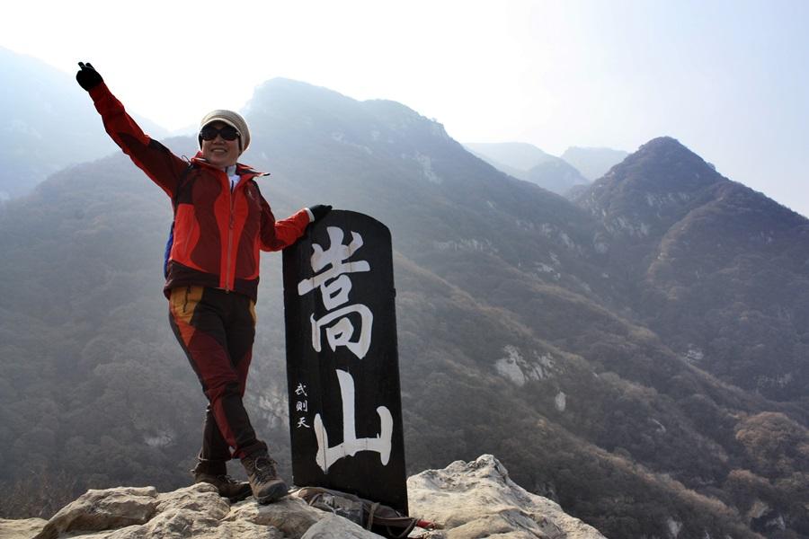중악 숭산 봉황대 정상에서 한 등산객이 손을 들어보이며 기념사진을 찍고 있다. 뒤에 보이는 산이 정상연천봉.