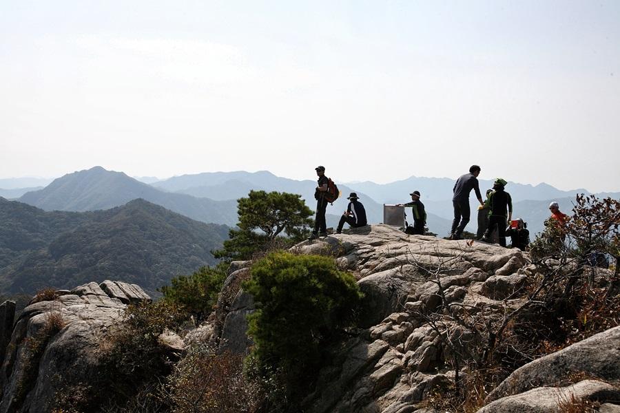 대야산 암벽 바위 위에서 등산객들이 조망을 하고 있다.