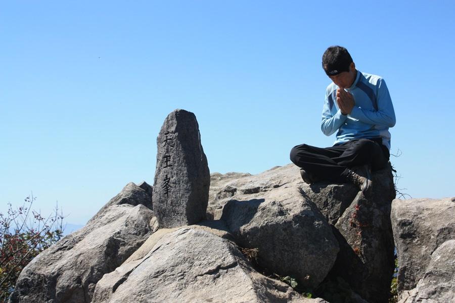속리산 정상 천왕봉에서 법주사를 향해 한 등산객이 기도를 올리고 있다.