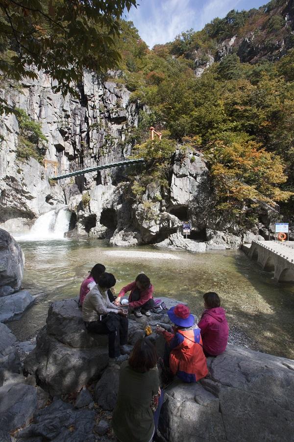 내연산 관음굴 앞에서 등산객들이 음식을 먹고 있다.